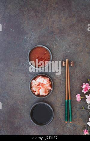 Sushi Set. Japanese sushi chopsticks,  soy and chili sauce bowl and pickled ginger on dark stone background - Stock Photo