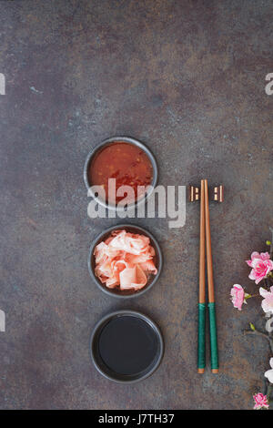 Sushi Set. Japanese sushi chopsticks,  soy and chili sauce bowl and pickled ginger on dark stone background - Stock Photo
