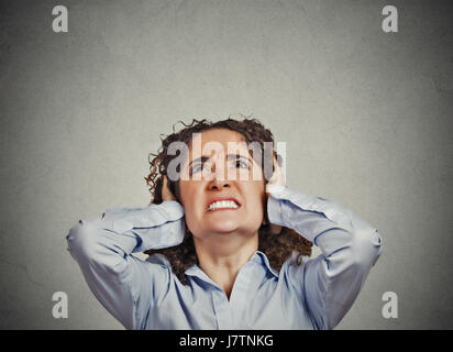 Closeup portrait young angry unhappy stressed woman covering her ears looking up stop making loud noise it's giving - Stock Photo