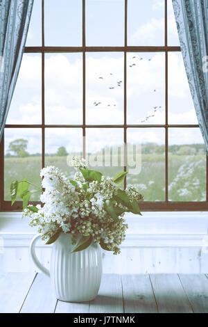 Lilac flowers in vase on a table by the window overlooking country field - Stock Photo