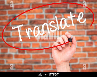 Man Hand writing Translate with black marker on visual screen. Isolated on bricks. Business, technology, internet - Stock Photo