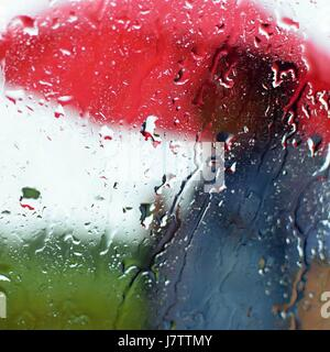 A man under an umbrella in the rain. Drops with a blurred background. - Stock Photo