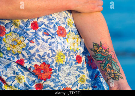 Young lady's wearing flowery t-shirt holding arm with colourful insect and flowers tattoo - Stock Photo