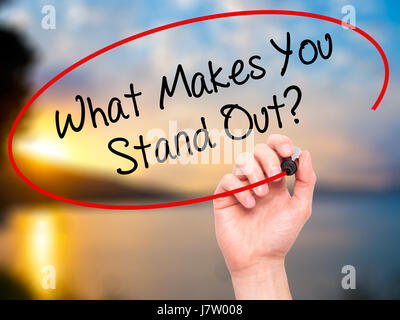 Man Hand writing What Makes You Stand Out? with black marker on visual screen. Isolated on background. Business, - Stock Photo