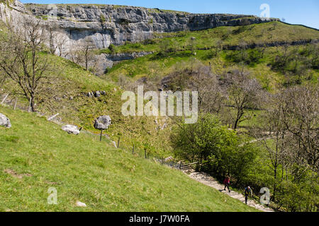 View of Malham Cove from Pennine Way path with people walking up. Malham, Malhamdale, Yorkshire Dales National Park, - Stock Photo