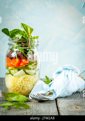 Colorful salad with couscous, tofu and vegetables in a jar. Love for a healthy vegan food concept - Stock Photo