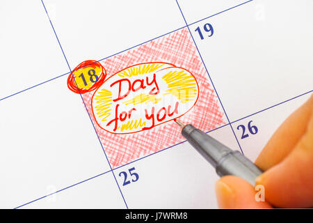 Woman fingers with red pen writing reminder Day for You in calendar. - Stock Photo