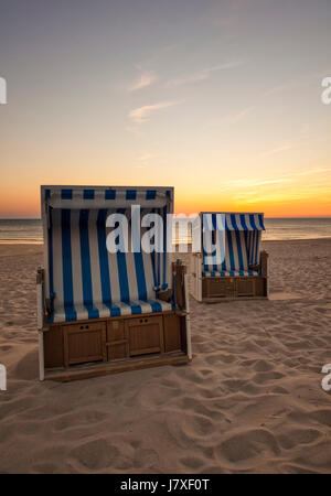 Two beach chairs at North Sea beach of Hornum, Sylt, in sunset - Stock Photo