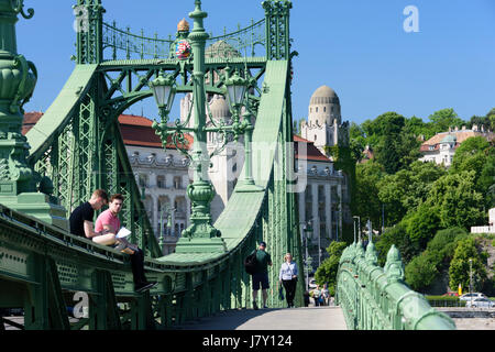 Hungary, Budapest. The Liberty Bridge. Students sitting on the bridge - Stock Photo