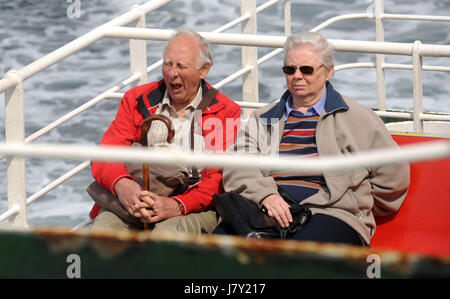 ELDERLY MAN YAWNING WHILST SITTING ON FERRY BOAT WITH ELDERLY LADY COUPLE RE COUPLES OAPS RETIREMENT UK - Stock Photo