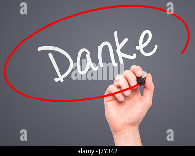 Man Hand writing Danke with marker on transparent wipe board. Isolated on grey. Business, internet, technology concept. - Stock Photo