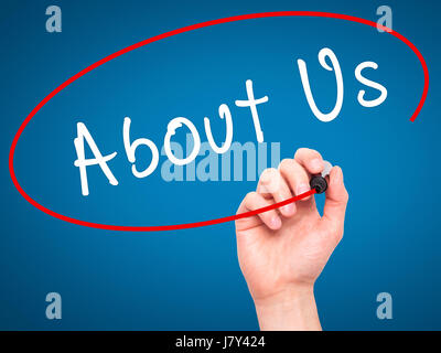Man Hand writing About Us with marker on transparent wipe board. Isolated on blue. Business, internet, technology - Stock Photo