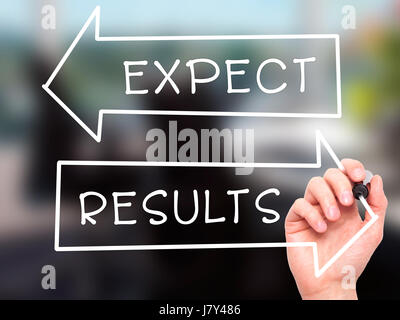 Man Hand writing Expect and Results with marker on transparent wipe board. Isolated on office. Business, internet, technology concept. Stock Photo