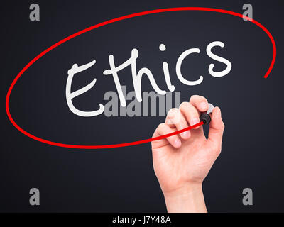 Man hand writing Ethics on visual screen. Business,help, internet, technology concept. Isolated on black. Stock - Stock Photo