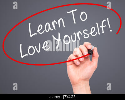 Man Hand writing Learn To Love Yourself with marker on transparent wipe board. Isolated on grey. Business, internet, - Stock Photo