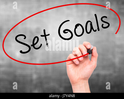 Man hand writing Set Goals on visual screen. Business,help, internet, technology concept. Isolated on grey. Stock - Stock Photo