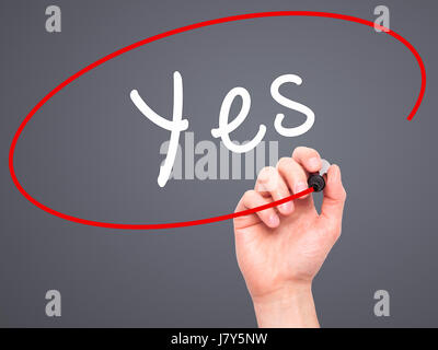 Man Hand writing Yes with black marker on visual screen. Isolated on grey. Business, technology, internet concept. - Stock Photo