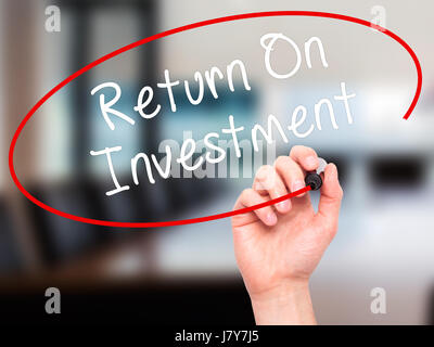Man Hand writing Return On Investment  with black marker on visual screen. Isolated on office. Business, technology, - Stock Photo