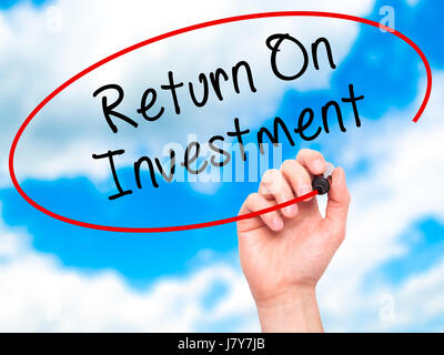 Man Hand writing Return On Investment  with black marker on visual screen. Isolated on sky. Business, technology, - Stock Photo