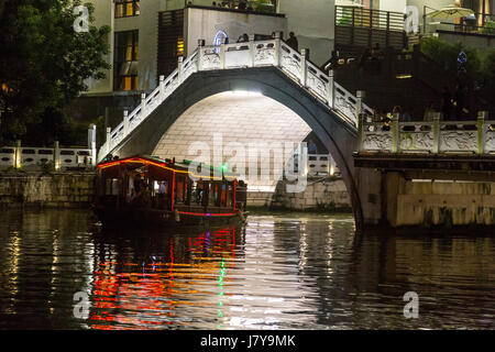 Wenzhou, Zhejiang, China.  Tourist Boat Passing under Bridge Over the Nantong River, at Night. - Stock Photo