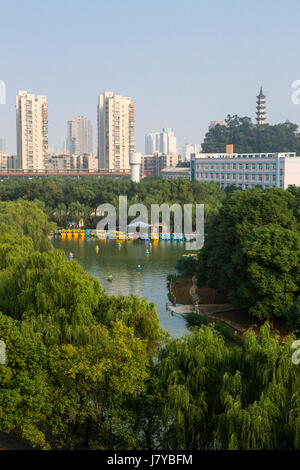Wenzhou, Zhejiang, China.  Apartment Buildings in Background, Recreational Boats on Lake in Foreground. - Stock Photo