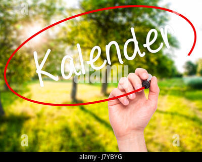 Man Hand writing Kalender (Calendar in German)  with black marker on visual screen. Isolated on nature. Business, - Stock Photo