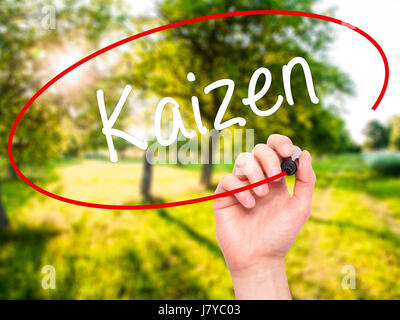 Man Hand writing Kaizen with black marker on visual screen. Isolated on nature. Business, technology, internet concept. - Stock Photo