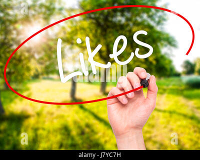 Man Hand writing Likes with black marker on visual screen. Isolated on background. Business, technology, internet - Stock Photo