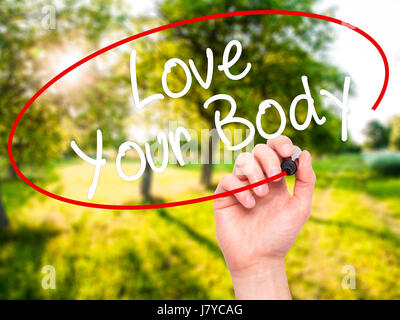Man Hand writing Love Your Body with black marker on visual screen. Isolated on nature. Business, technology, internet - Stock Photo