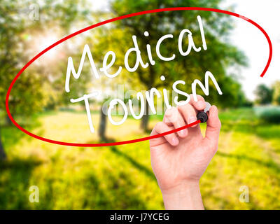 Man Hand writing Medical Tourism with black marker on visual screen. Isolated on nature. Business, technology, internet - Stock Photo