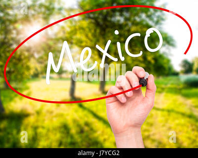 Man Hand writing Mexico  with black marker on visual screen. Isolated on nature. Business, technology, internet - Stock Photo