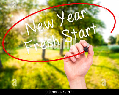 Man Hand writing New Year Fresh Start with black marker on visual screen. Isolated on nature. Business, technology, - Stock Photo