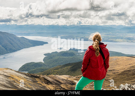 Female hiker looking at the South Fiord of Lake Te Anau, Southern Alps at back, hiking trail Kepler Tack - Stock Photo