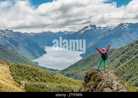 Female hiker looking at the South Fiord of Lake Te Anau, arms outstretched, Southern Alps at back, hiking trail - Stock Photo