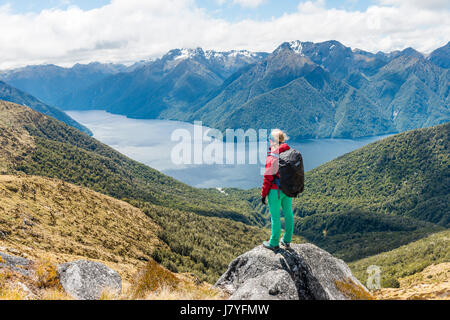 Female hiker looking at the South Fiord of Lake Te Anau, Southern Alps at back, Kepler Tack, Fiordland National - Stock Photo