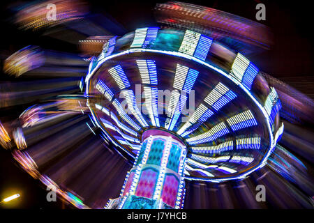 Long exposure shot of the popular Wave Swinger ride, with ghost trails of the riders.  Playland, Vancouver B.C. - Stock Photo