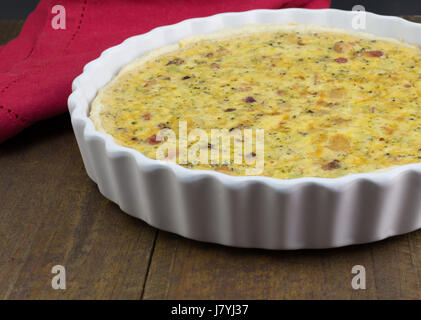 Quiche with cheese, bacon and mushroom on rustic wooden table - Open pie in white dish with selective focus - Stock Photo