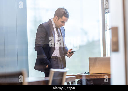 Businessman looking at smart phone in modern corporate office. - Stock Photo