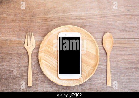Top view smartphone in wooden dish, spoon and fork on wooden plank background. Eating technology concept - Stock Photo