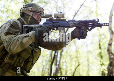 Military sniper on task in woods during day - Stock Photo
