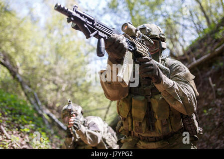 Group officers on military mission in woods during day - Stock Photo