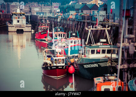 WHISTABLE, UITED KINGDOM - January 21, 2017: Fishing Boats and fisherman's sheds in Whitstable Harbour - Stock Photo