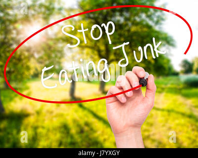 Man Hand writing Stop Eating Junk with black marker on visual screen. Isolated on background. Business, technology, - Stock Photo