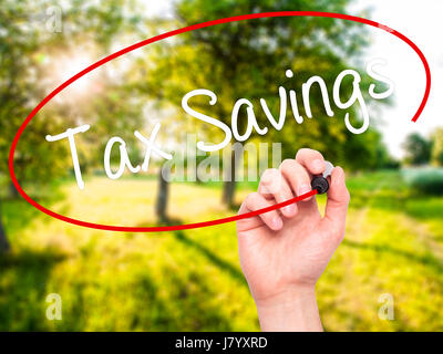 Man Hand writing Tax Savings with black marker on visual screen. Isolated on background. Business, technology, internet - Stock Photo