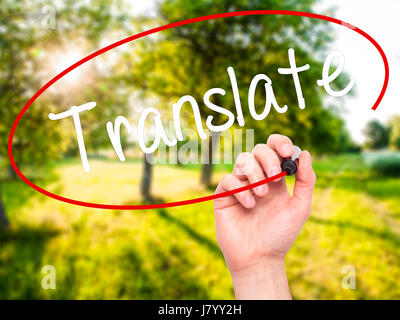 Man Hand writing Translate with black marker on visual screen. Isolated on nature. Business, technology, internet - Stock Photo