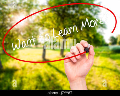Man Hand writing Want to Learn More? with black marker on visual screen. Isolated on nature. Business, technology, - Stock Photo