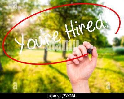 Man Hand writing You're Hired! with black marker on visual screen. Isolated on nature. Business, technology, internet - Stock Photo
