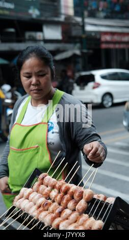 Open Air Street Vendors cooking Thai Food on Yaowarat Road in Chinatown Bangkok Thailand - Stock Photo
