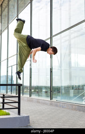 Young man jumps on a railing. Parkour in the urban space. Sports in the city. Sport activity. - Stock Photo