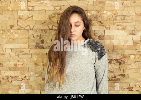 Sad teenage girl hair covering face looking down - Stock Photo